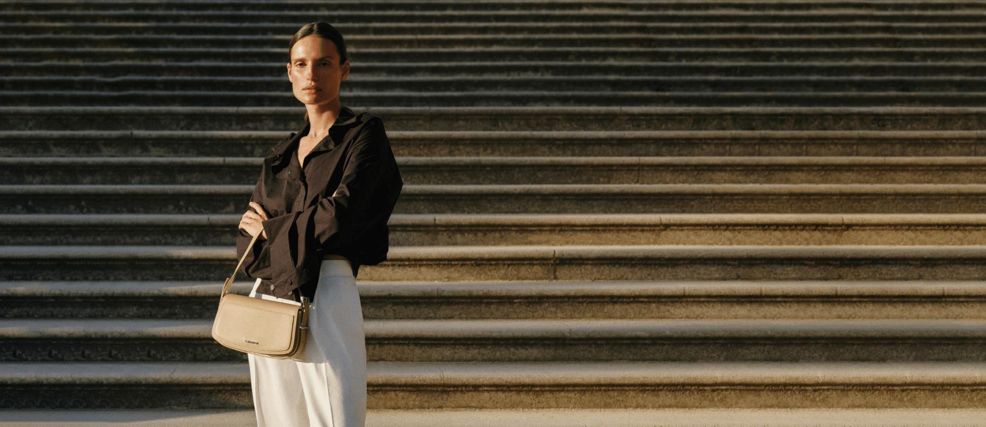 Kobieta z beżową torebką oraz w czarnej koszuli